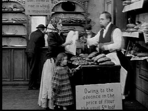 stockvideo's en b-roll-footage met 1909 b/w wide shot baker selling bread with signs explaining higher prices/ woman paying/ woman giving bread back and leaving - 1900 1909