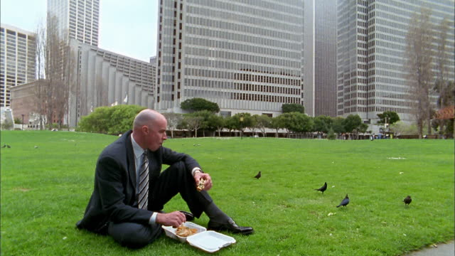 Wide shot bald businessman eating lunch on lawn / tilt up to skyscrapers