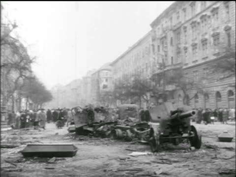 B/W 1956 wide shot battered vehicles in city street / crowd in background / Hungarian uprising