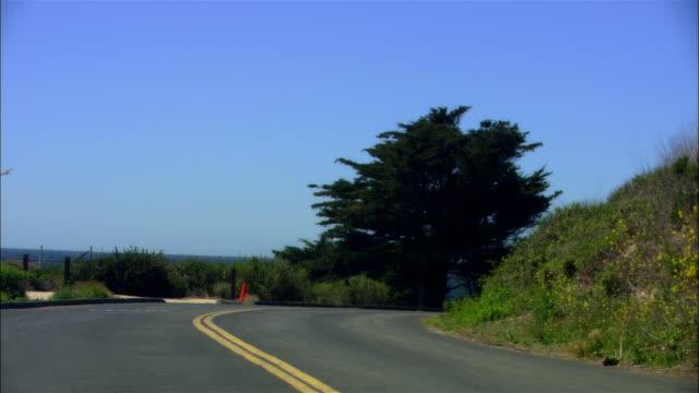 vídeos de stock e filmes b-roll de wide shot bend in road with beach and ocean horizon/ malibu, california - pacífico norte