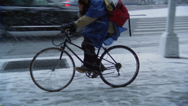 vídeos de stock, filmes e b-roll de wide shot bike messenger or delivery person riding bicycle on sidewalk on snowy day / new york city - entregador