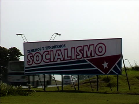 "2003 wide shot billboard promoting socialism (""socialismo"") along highway / traffic in background / cuba - socialism stock videos & royalty-free footage"