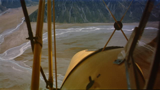 wide shot biplane cockpit point of view over valley with snowcovered mountains / making ascent / new zealand - propeller stock videos & royalty-free footage