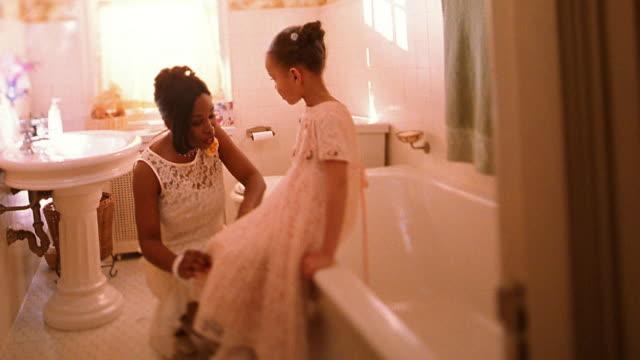 Wide shot Black bride kneeling beside small Black girl / adjusting her dress in bathroom