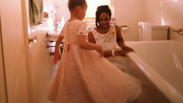 wide shot black bride watching small black girl spinning in dress in bathroom - dress stock videos & royalty-free footage