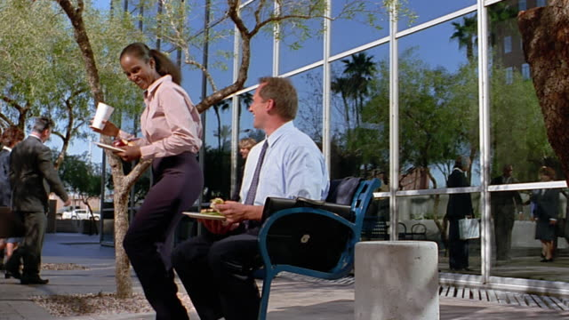 Wide shot Black businesswoman siting down on bench next to businessman / eating lunch