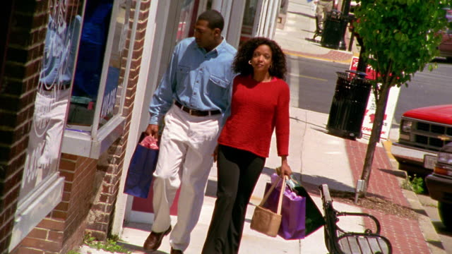 Wide shot Black couple walking down street with shopping bags / Havre de Grace, Maryland