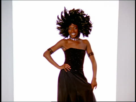 wide shot black female model in formalwear walking on catwalk and tripping / zoom in to medium shot she trips again / tilt down tilt up - runway stock videos & royalty-free footage