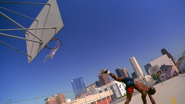 CANTED wide shot PAN Black man doing cartwheel with basketball + dunking basketball on outdoor court
