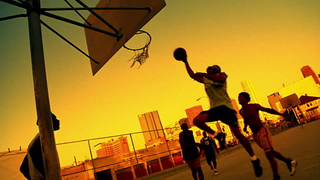 SEPIA CANTED wide shot Black man doing lay-up shot in pickup basketball game on outdoor court / Los Angeles