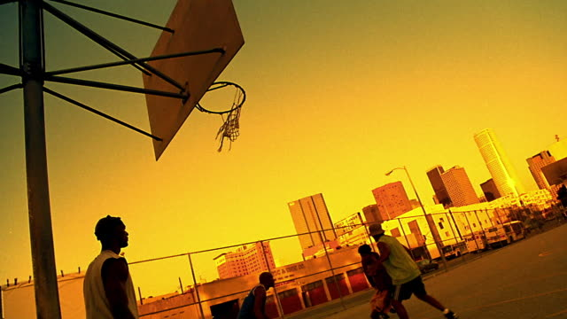 sepia canted wide shot black man doing lay-up shot in pickup basketball game on outdoor court / los angeles - generic location stock videos & royalty-free footage