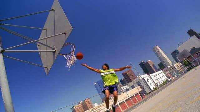 vídeos y material grabado en eventos de stock de canted wide shot black man dunking basketball from high bounce on outdoor court / los angeles - mate técnica de vídeo