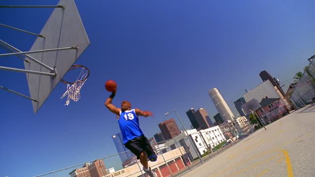 vídeos y material grabado en eventos de stock de canted wide shot black man dunking basketball + talking to camera on outdoor court / los angeles - mate técnica de vídeo