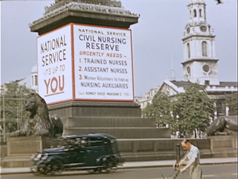 vidéos et rushes de wide shot black taxi and doubledecker bus passing st martininthefields church and nelson's column wrapped with civil nursing reserve sign reading... - écriture européenne