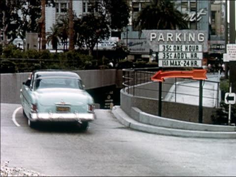 vídeos y material grabado en eventos de stock de 1956 wide shot blue chrysler imperial driving into an underground parking garage - escritura occidental