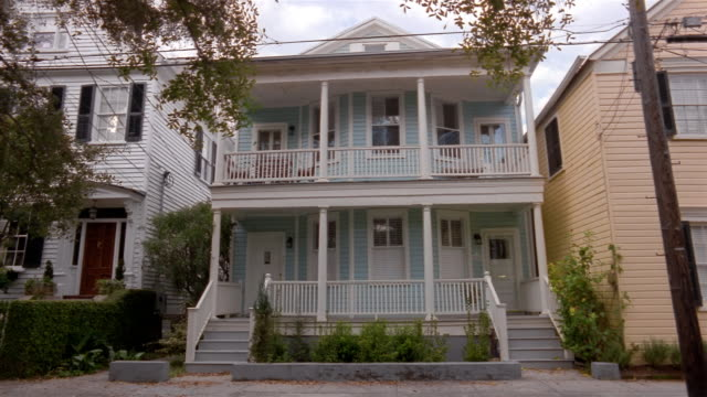 wide shot blue semi-detached house with porch/ charleston, south carolina - 建物の正面点の映像素材/bロール