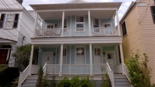 Wide shot blue semi-detached house with porch/ Charleston, South Carolina