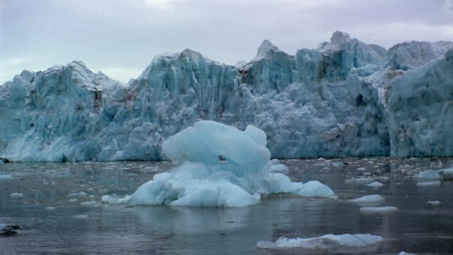 wide shot boat point of view iceberg and ice floes floating in front of glacier / arctic - nick berg stock videos & royalty-free footage