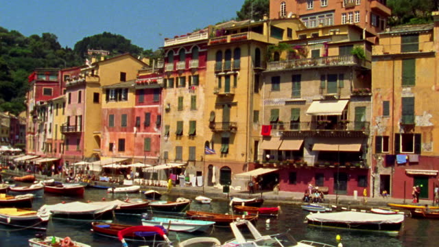 wide shot Boat point of view past boats docked in front of town / Portofino, Italy
