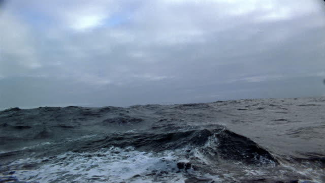 Wide shot boat point of view rough sea on overcast day / Arctic