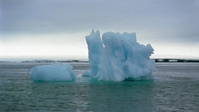 wide shot boat point of view two icebergs floating in water / arctic - nick berg stock videos & royalty-free footage