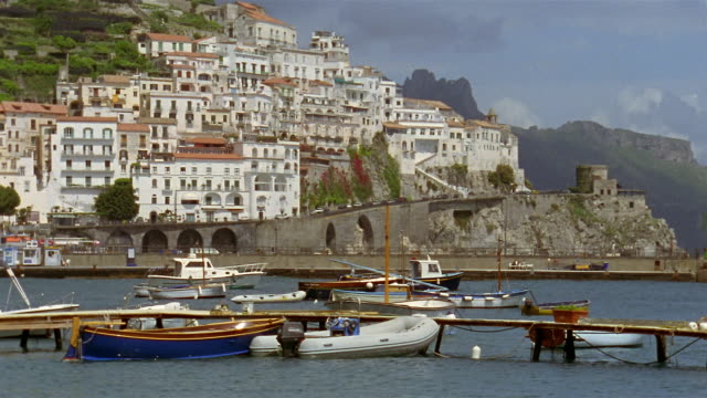 Wide shot boats docked in Gulf of Salerno with hillside town of Amalfi in background / Amalfi Coast, Campania, Italy