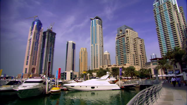 vídeos y material grabado en eventos de stock de wide shot boats in marina with skyscrapers in background/ dubai - grupo mediano de objetos