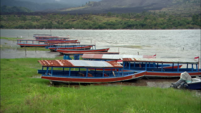 wide shot boats moored on the shore of lake kintamani / bali, indonesia - medium group of objects stock videos & royalty-free footage