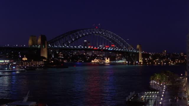 Wide shot boats passing in harbour under Sydney Harbour Bridge/ Sydney, Australia