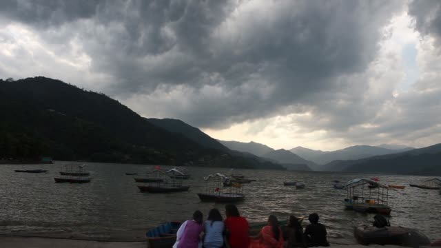 Wide shot boats sit on Phewa lake in Pokhara Nepal Wide shot an information board stands on the shore of Phewa lake in Pokhara Wide shot people sit...