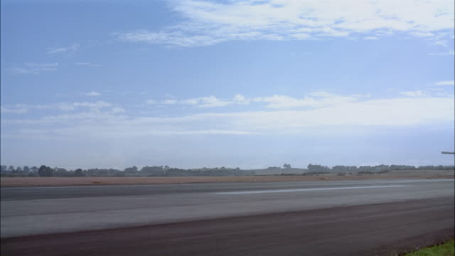 Wide shot Boeing 747 speeding past CAM on runway at Auckland International Airport / Mangere, New Zealand