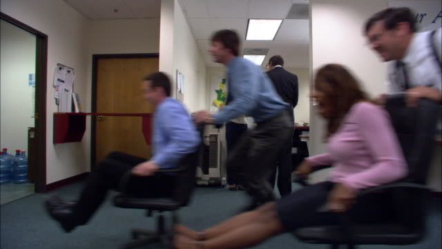 wide shot boss talking to employee in background / employees racing by on office chairs behind boss's back / low angle - wasting time stock videos & royalty-free footage