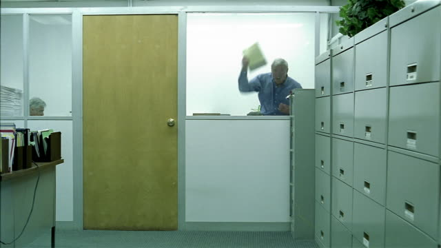 wide shot boss yelling at employee in office room / tracking shot employee leaving room and walking through office - filing cabinet stock videos & royalty-free footage