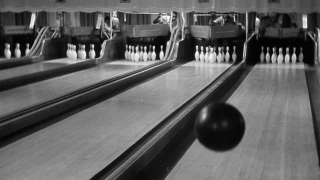 b/w wide shot bowling ball bouncing across two lanes in bowling alley with men behind lanes - ボーリングボール点の映像素材/bロール