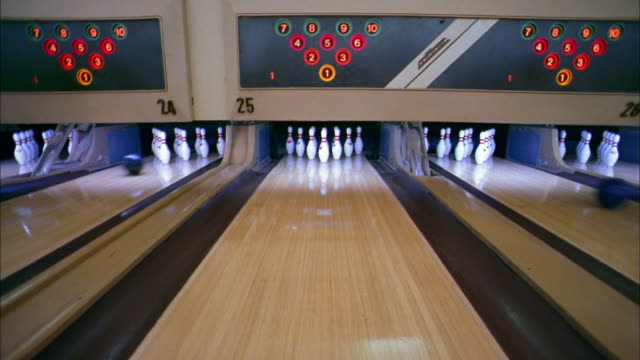 vídeos de stock, filmes e b-roll de wide shot bowling ball knocking pins over for strike - cancha de jogo de boliche