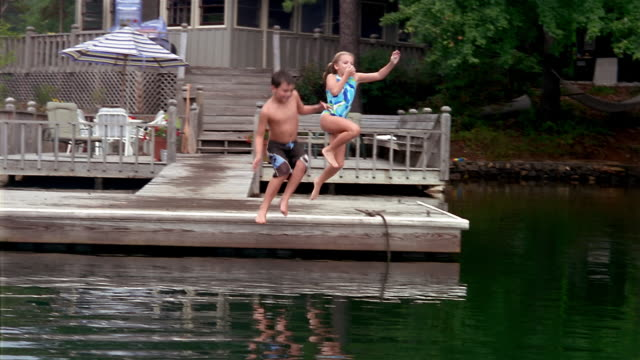 Wide shot boy and girl in bathing suits running to end of dock + jumping into lake