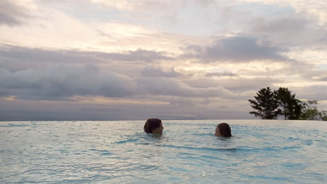 Wide shot boy and girl jumping into infinity pool / medium shot swimming toward CAM / smiling at CAM / South Africa