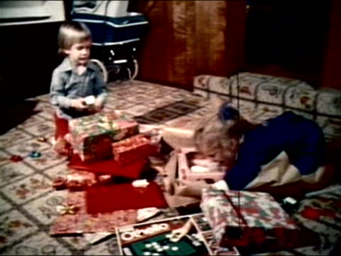 1977 wide shot boy and girl opening pile of hannukah gifts on living room floor - gift stock videos and b-roll footage