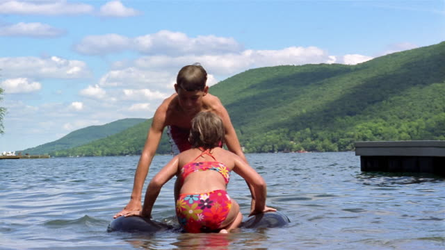 wide shot boy and girl trying to balance on inner tube in lake / falling off / canandaigua lake, new york - nur kinder stock-videos und b-roll-filmmaterial