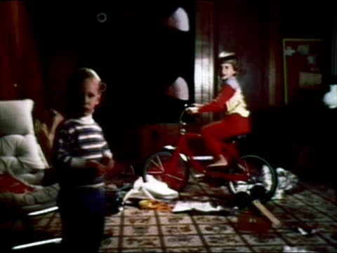 1979 wide shot boy in living room on bike with training wheels received as hanukkah gift as younger brother looks on - stabilisers stock videos & royalty-free footage