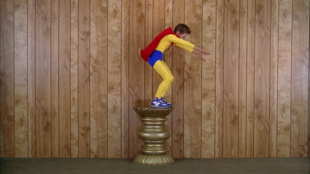 Wide shot boy in super hero costume standing on pedestal and pretending to fly