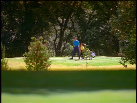 wide shot PAN boy + man pulling golf bag walking on golf course