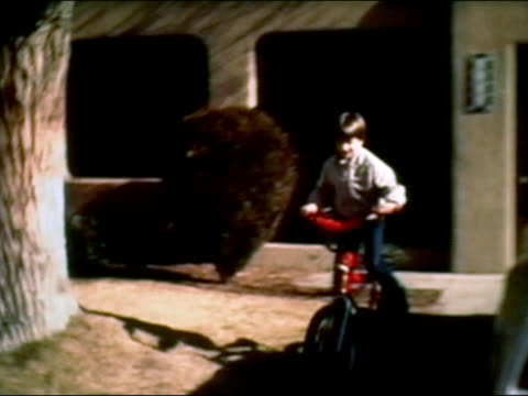 stockvideo's en b-roll-footage met 1983 wide shot boy riding bike down suburban driveway - 1983