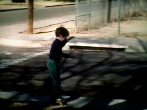 stockvideo's en b-roll-footage met 1983 wide shot boy roller skating on suburban sidewalk - 1983