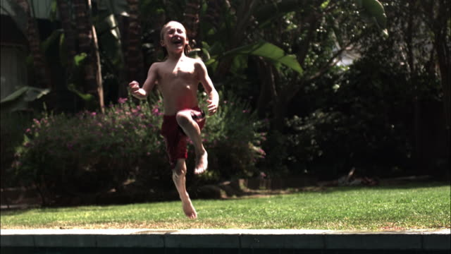 Wide shot boy running, jumping, and doing a cannonball in swimming pool