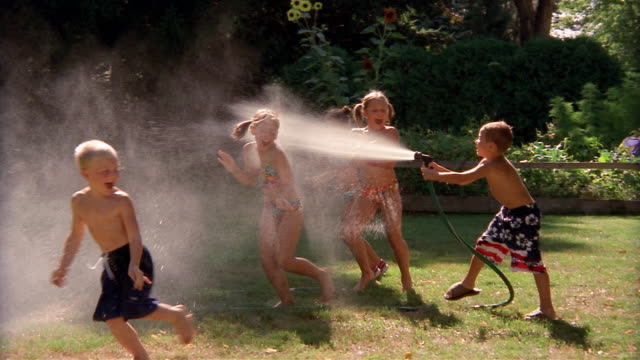 wide shot boy spraying row of children with water hose / children running away / new york - messing about stock videos & royalty-free footage
