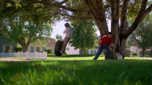 wide shot boy standing in tire swing / older boy playing w/dog in yard - tire swing stock videos & royalty-free footage