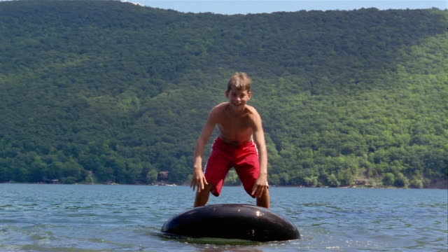 wide shot boy standing up and balancing on inner tube in lake / falling off / canandaigua lake, new york - 水泳用浮き輪点の映像素材/bロール