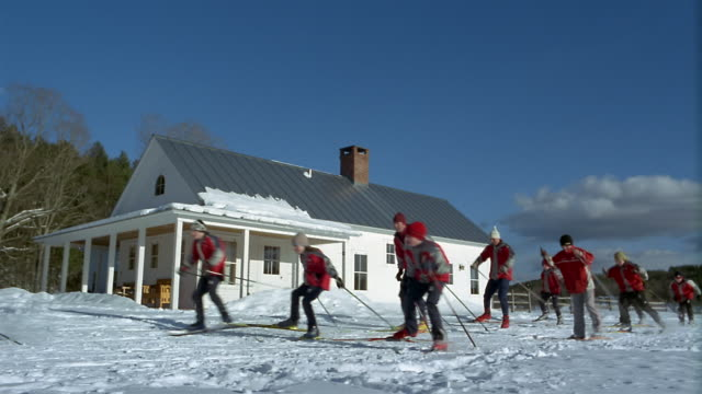 wide shot boys cross-country ski team and coaches skiing past lodge / vermont - vermont stock videos & royalty-free footage