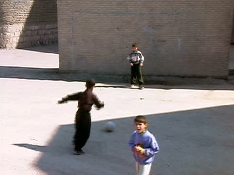 Wide shot Boys playing soccer in empty lot near brick wall/ Turkey